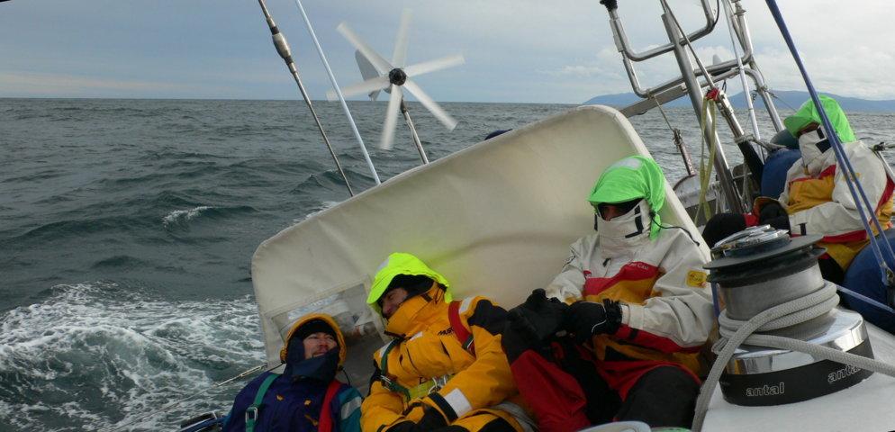 5 persone in navigazione di poppa in oceano e coperti per il freddo